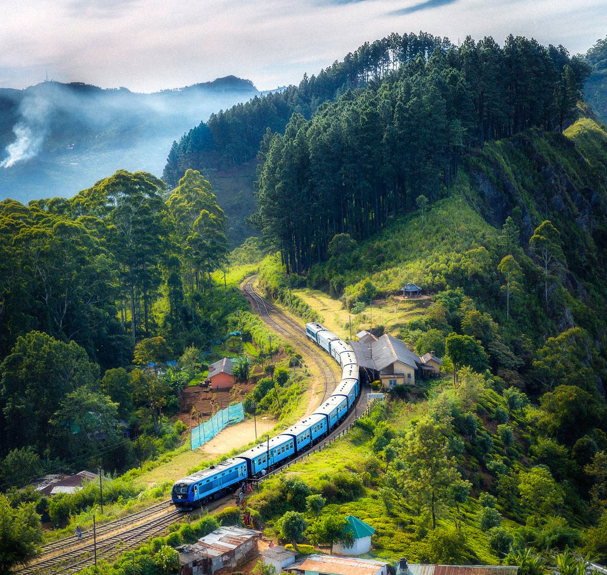 Photo of a train in misty mountains with forest in the background. Photo by: SenuScape / Pexels
