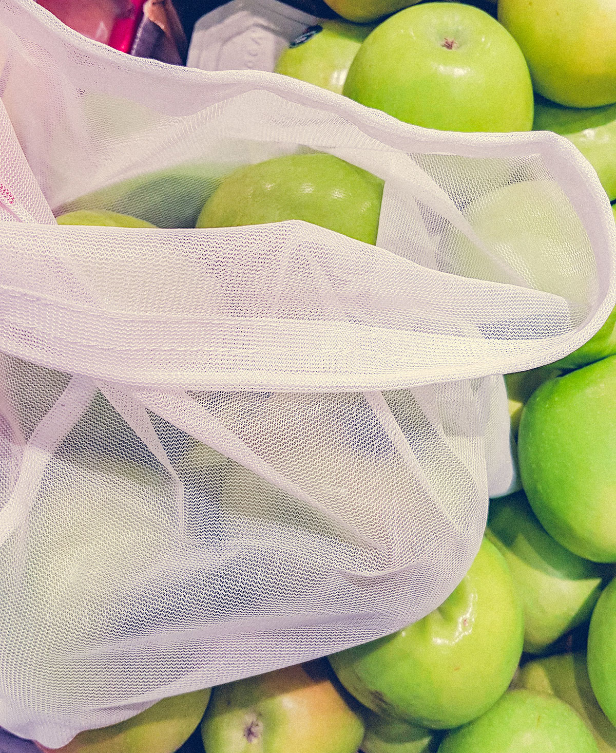 Photo of apples in produce section at store with fabric produce bag